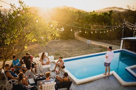 People hanging out with each other on patio with pool