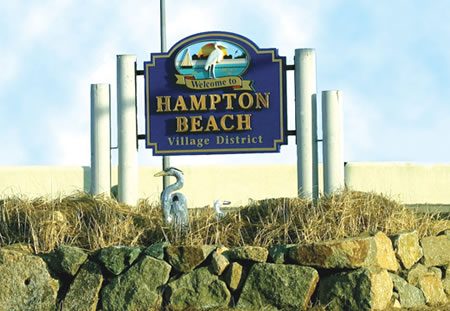 A green sign at the entrance of Hampton Beach standing on a rocky wall.