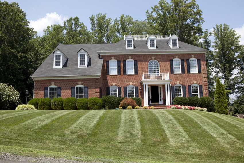 a brick house with a mowed lawn