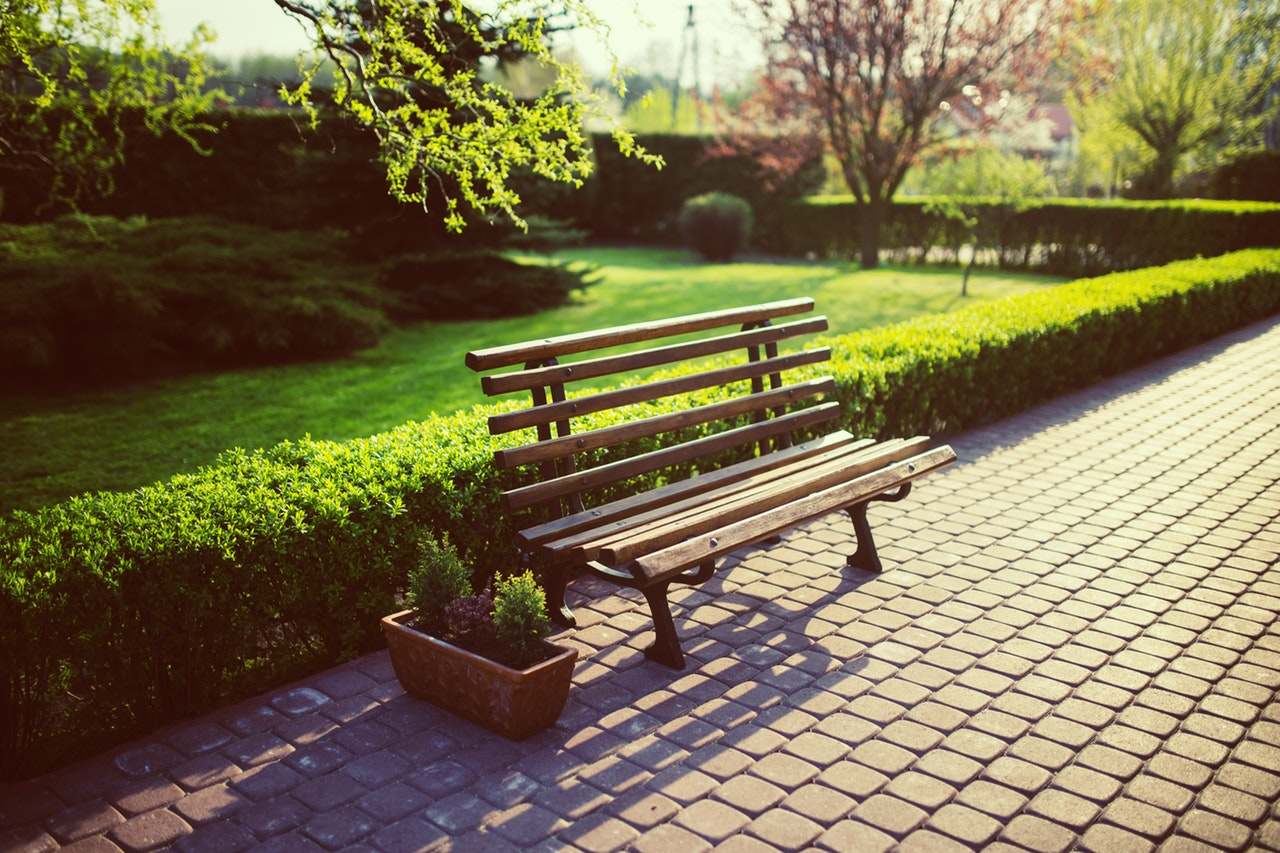 Park bench resting on a stone pathway in the middle of a park.