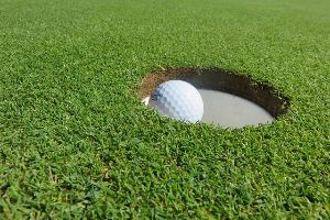 putting green on a golf course with a golf ball in the hole