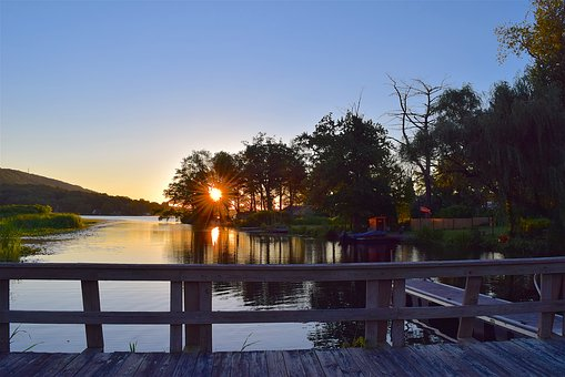 A lake with a wooden dock under a sunset on Apex farm in NC.