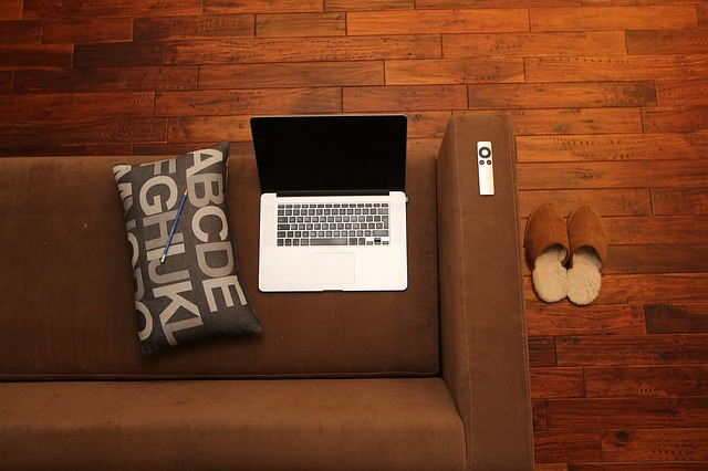 An accent pillow and laptop on a brown couch in a living room.