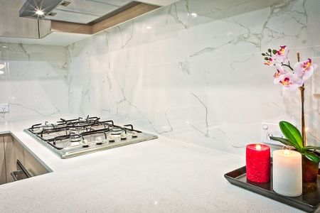 A brightly lit kitchen nook with white granite countertops and beige cabinets.