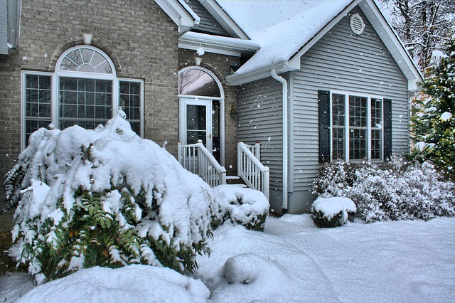 A single-family house with a brick and siding exterior that is covered in snow.