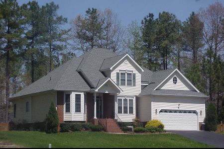 A two-story house with white siding in front of a line of trees.