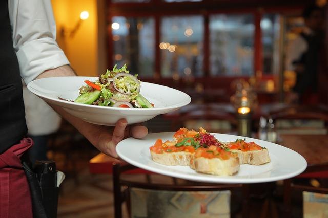 waiter holding plates at upscale restaurant