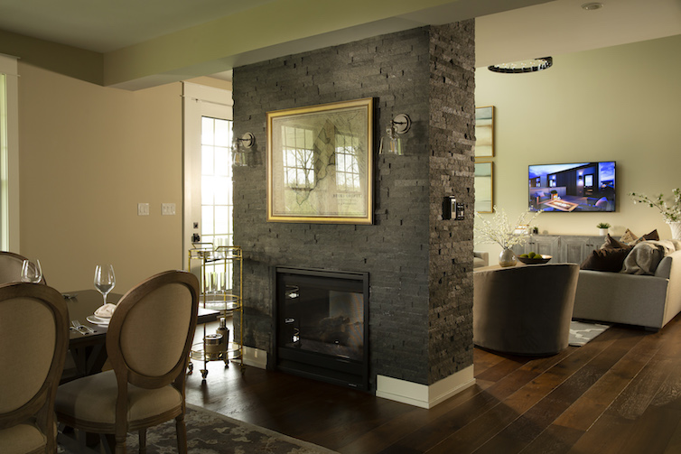 Dark stone fireplace with small view of open concept