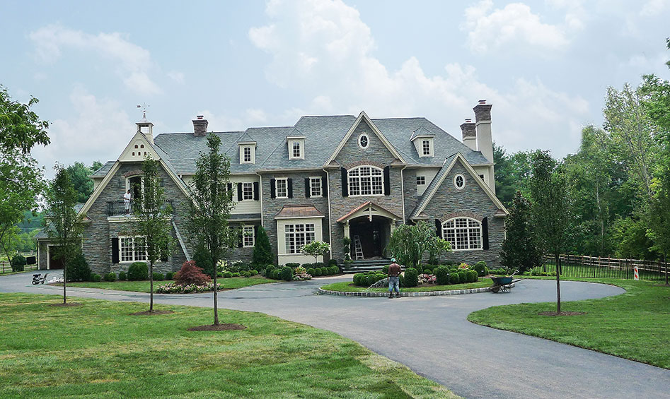 front of greenish-gray mansion with circle driveway