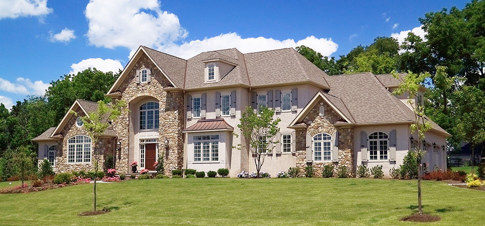 front of large brown stone home