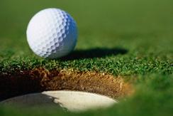 golf ball sitting near the hole