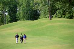 three golfers walking on the golf course