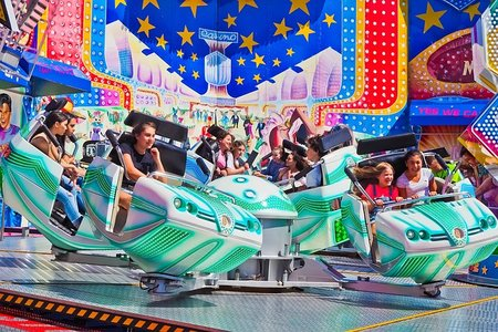 people sitting on a spinning ride at the fair