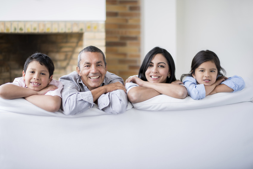 family sitting on a couch in a Briar Chapel home