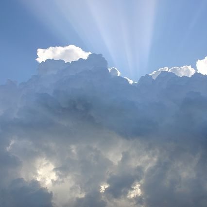 A ray of sunshine bursting through white clouds against a blue sky.