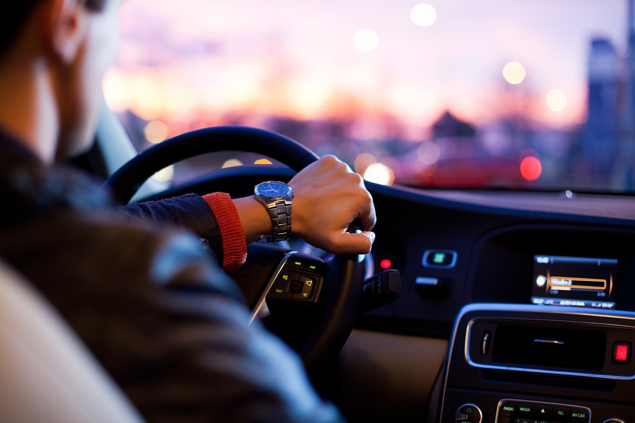 Man driving in a car at twilight.