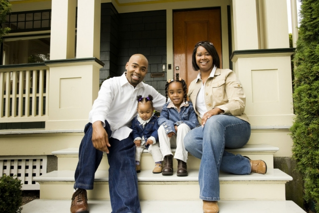 Home buyers sitting on the front porch of their new home