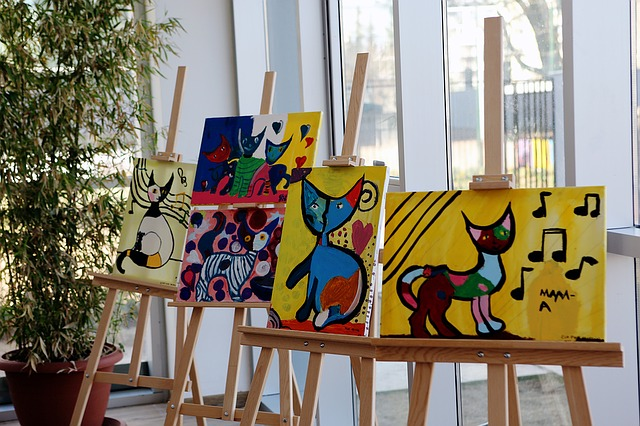 easels holding bright and colorful abstract paintings of cats