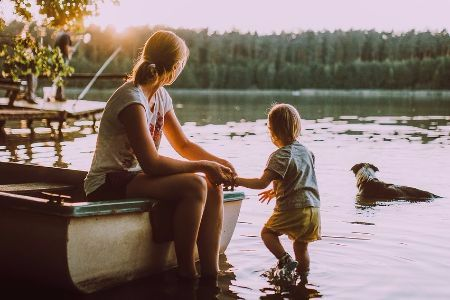 a mother and child and dog sitting on a boat looking out at the sunset