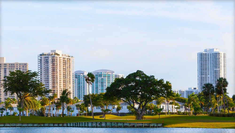 The rolling greens of a golf course framed by single-family homes and high-rise condos in the background.