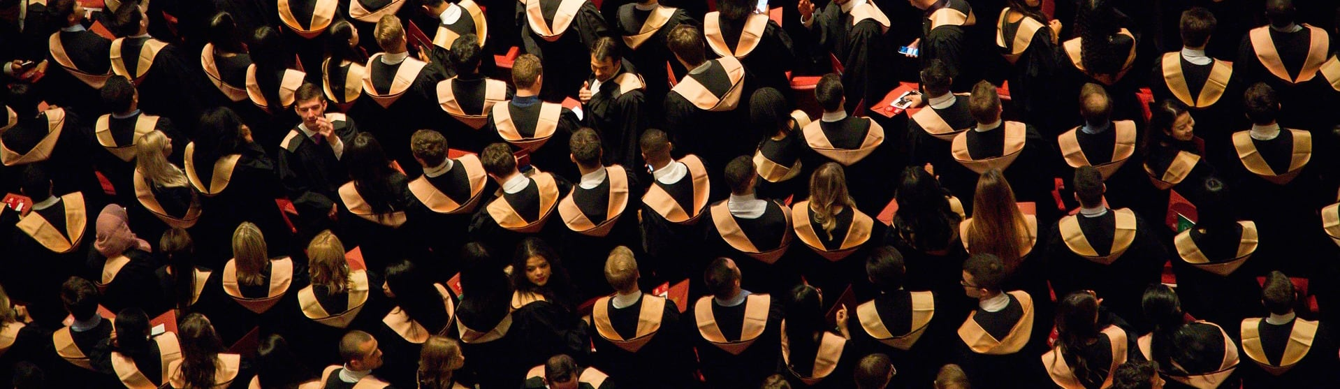 Aerial view of college graduates dressed in black robes and caps.