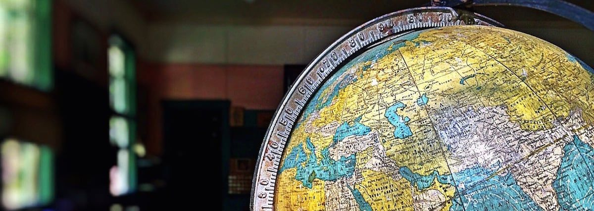 A colorful globe sitting in a classroom.