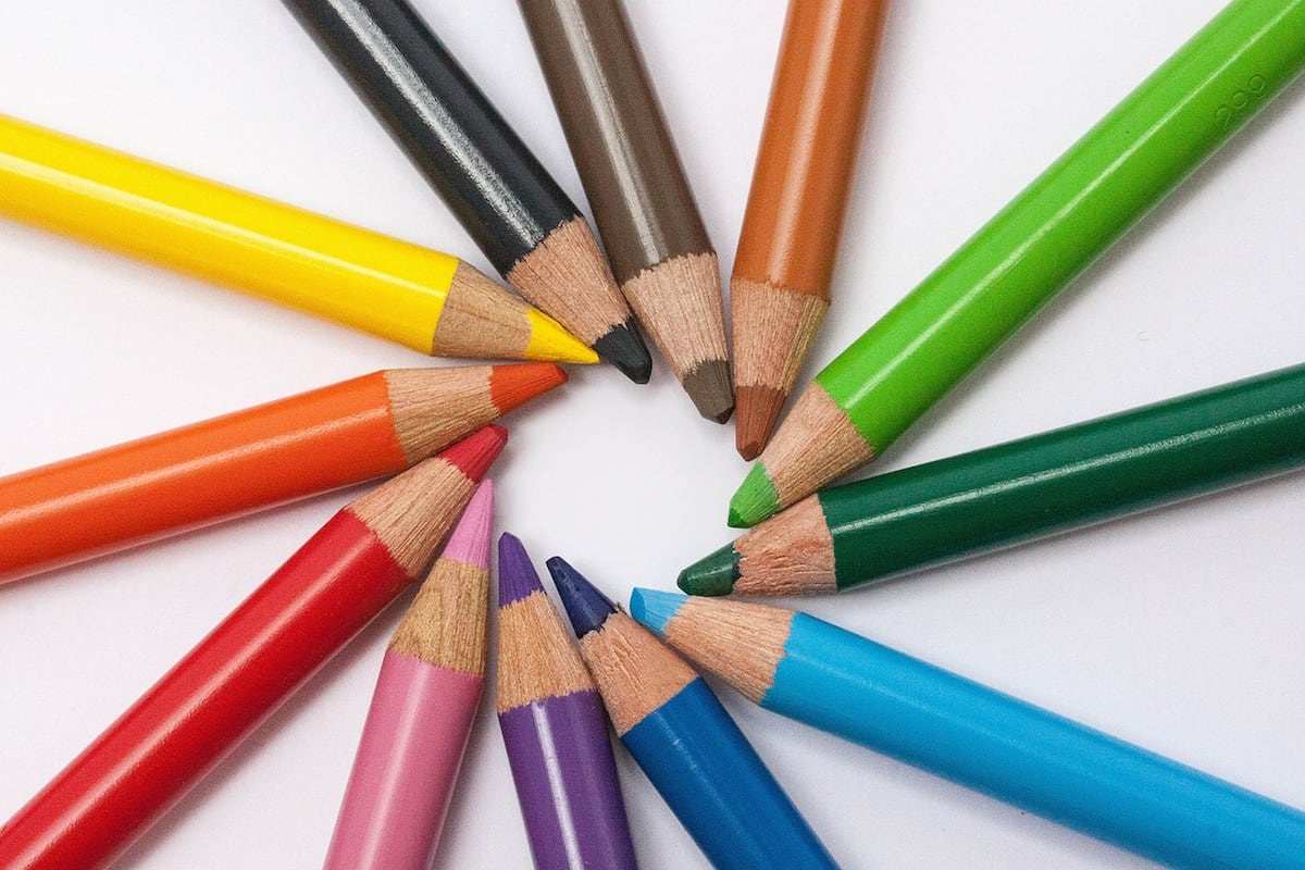 A rainbow of colored pencils arranged in a circle with tips facing toward the center of the circle.