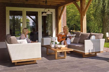 Two mature women chatting over tea while sitting on the patio.