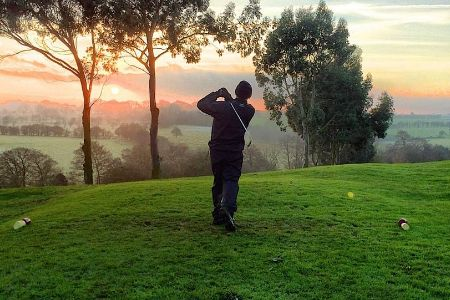 A golfer teeing off on a course overlooking a river.
