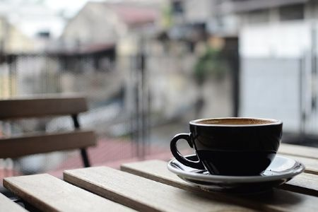 A mug full of coffee resting on a wooden table outside of a cafe.