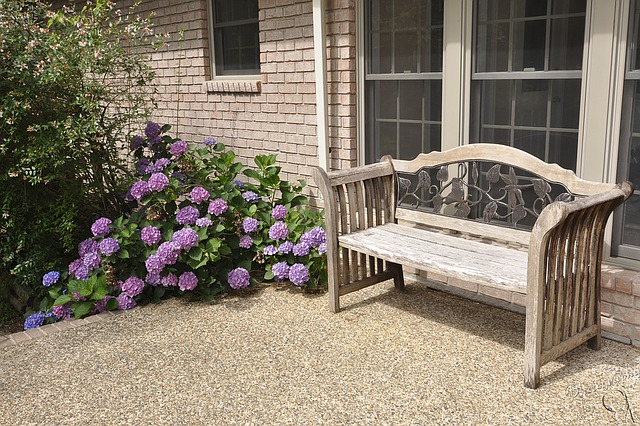A wooden bench on a patio overlooking a purple shrub.