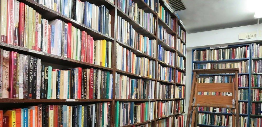 A tall bookshelf filled with paperback novels.