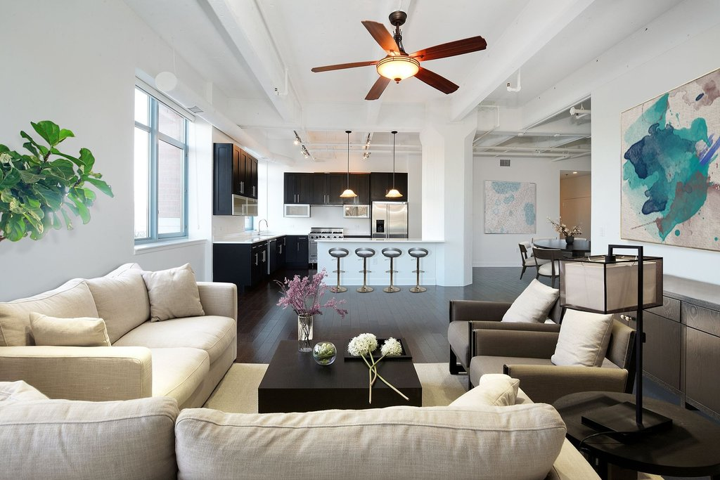 A living room with white couches that opens to a kitchen with modern designed cabinets and a tabletop with bar stools.