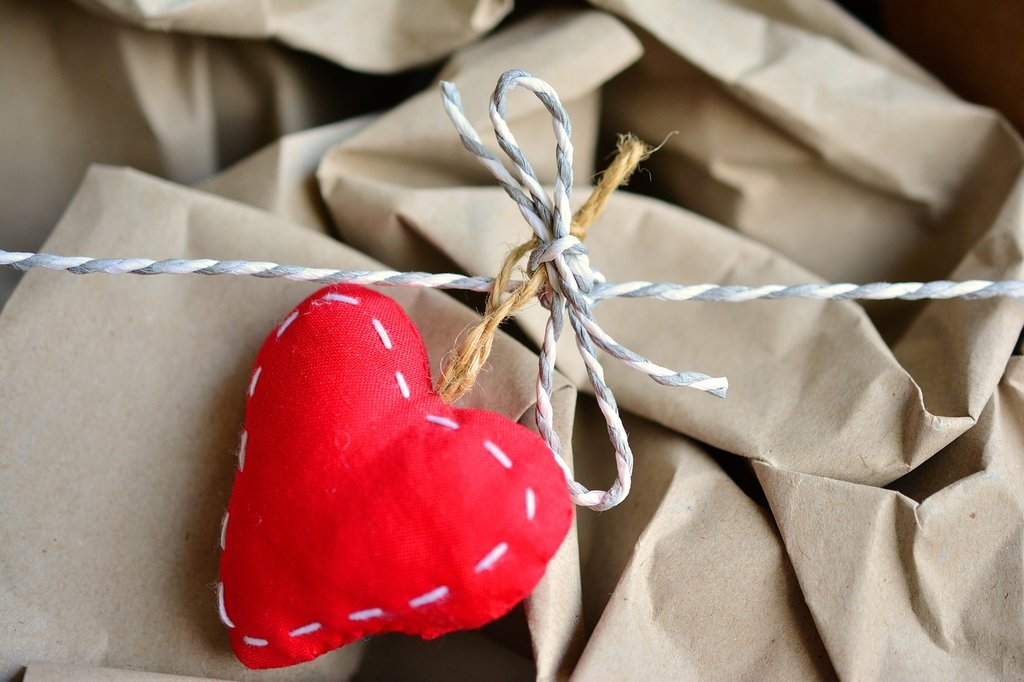 A red felt heart tied around a cardboard box filled with coffee cups.