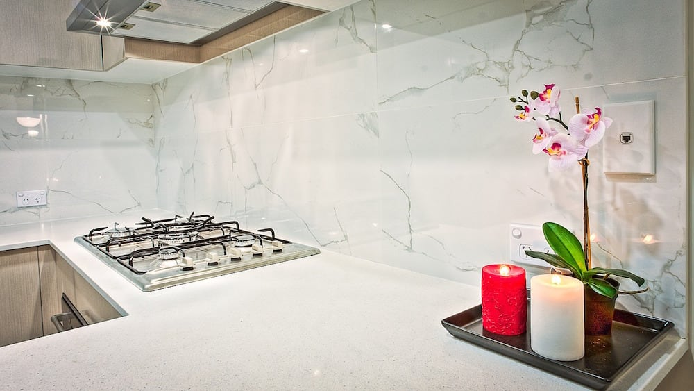 A modern and sparsely decorated kitchen with granite countertops, marble backsplash, and white cabinets.