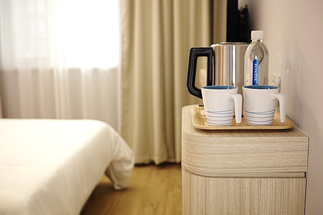 A brightly lit hotel room with coffee mugs and water on a nightstand.