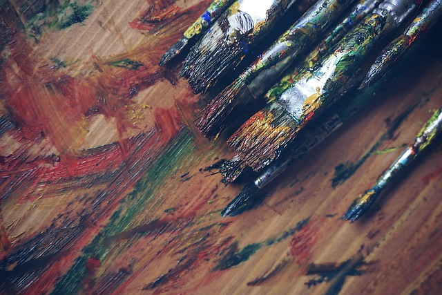Paint-covered brushes on a wooden table that is streaked with acrylic paint.