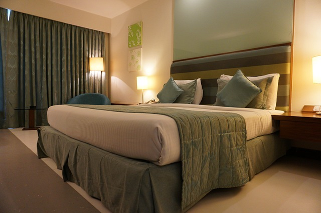 A large hotel bedroom draped in green comforters and sheets.