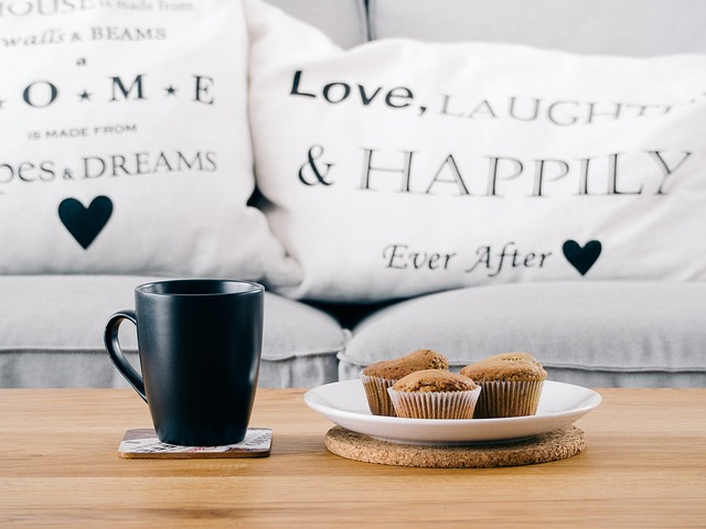 A wooden coffee table with a coffee mug and plate of muffins in front of a beige couch.