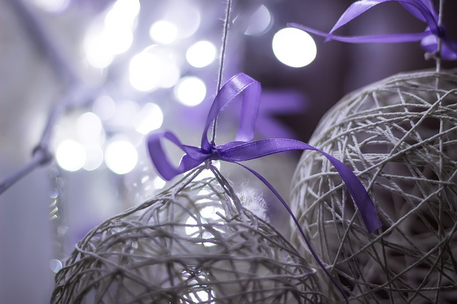 An ornament made of twine that is hanging with a purple ribbon.