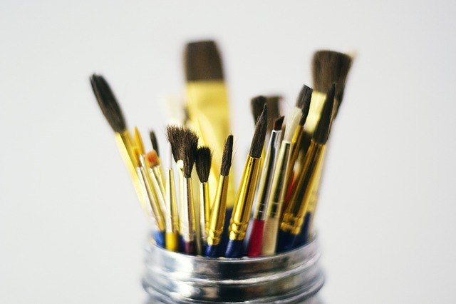 A glass jar full of paint brushes with the tips sticking up.