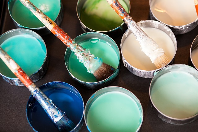 Cups of blue and green paint with paint brushes sticking out of them.