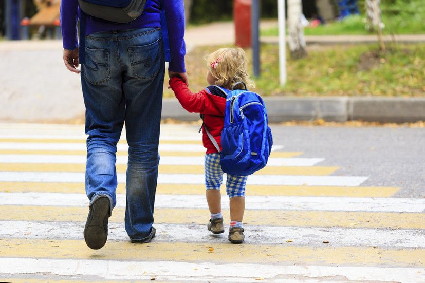 parent and child crossing the street together