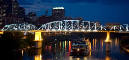 river at night in nashville with the bridge and tour boat in foreground