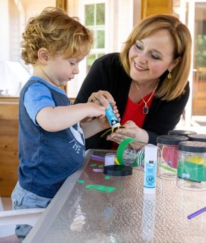 Julie helping small child with crafts