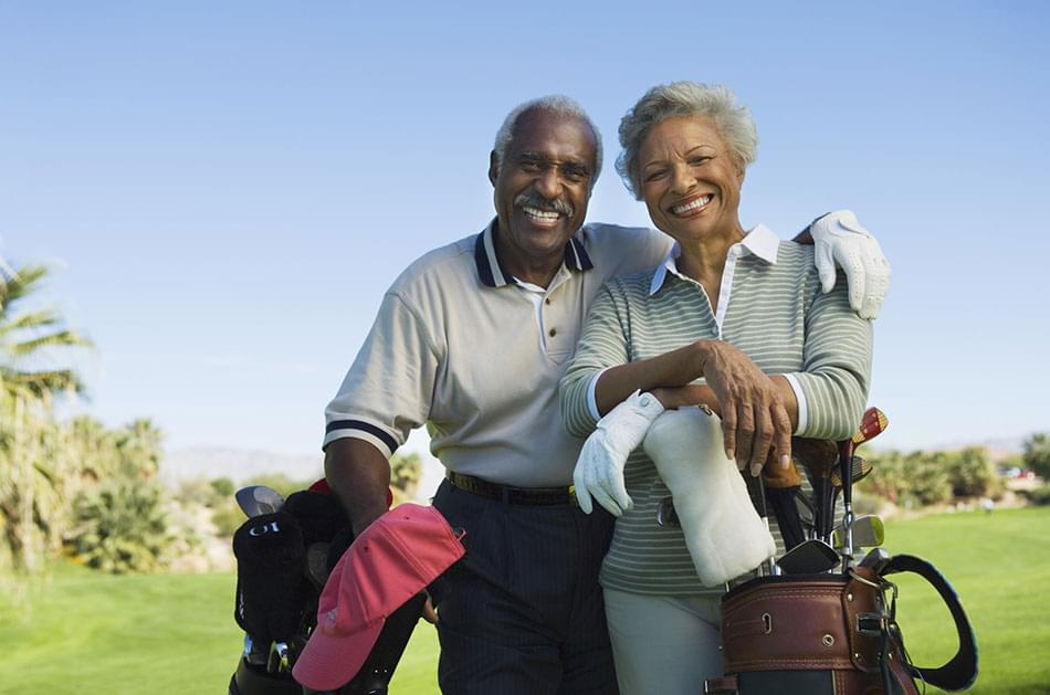 Couple smiling and playing golf