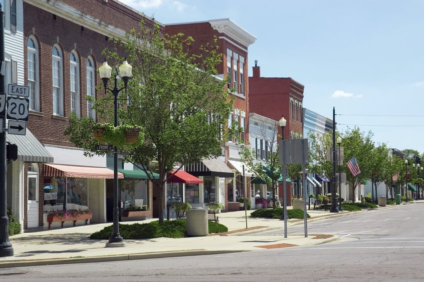 A main street in a small town, lined with vintage brick buildings and storefronts.