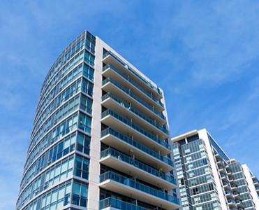 View of condo rising into a blue sky