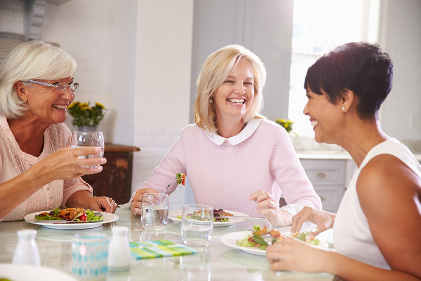 friends enjoying dinner in a home at del webb at traditions
