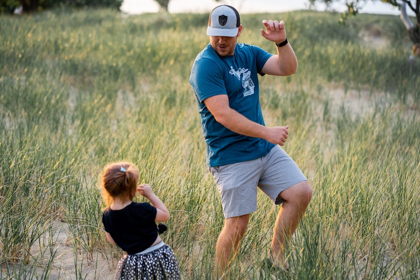 father and daughter dancing in field